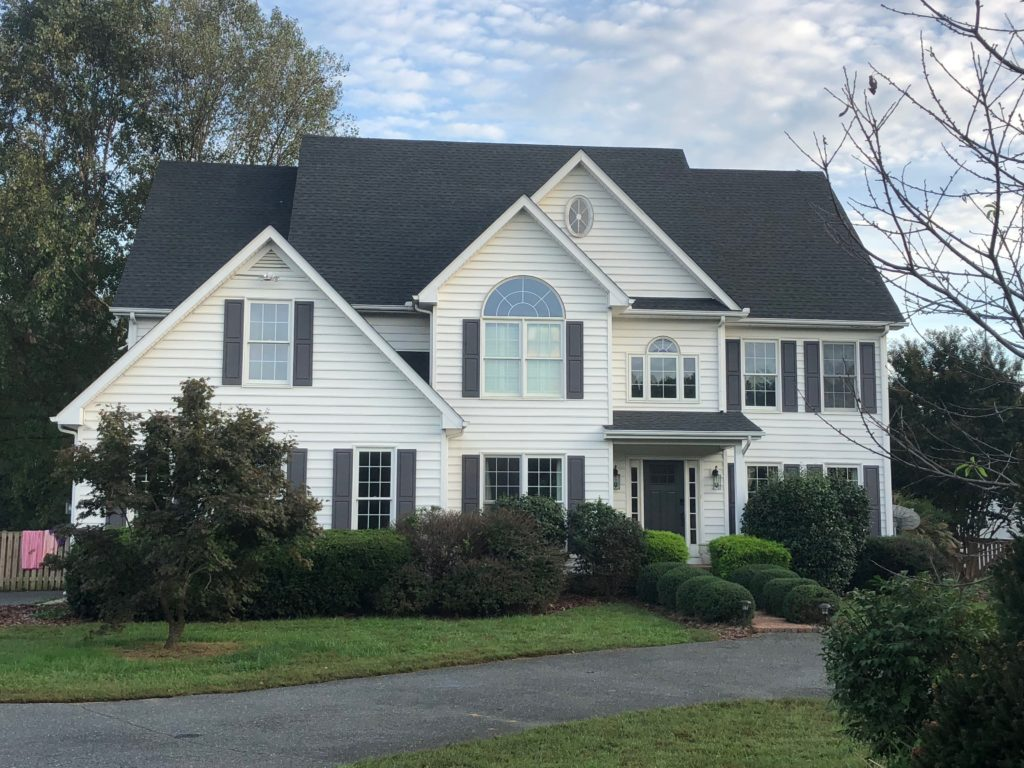 A white home with grey shingles installed by a roofing company in Maryland