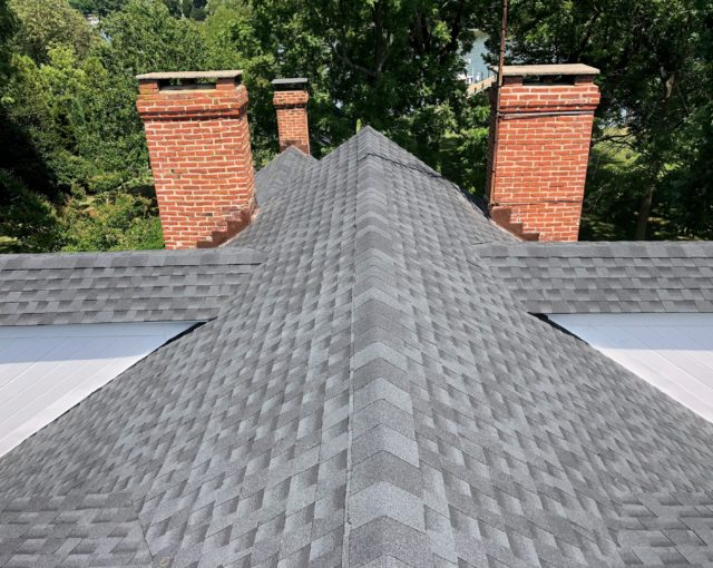 roof shingles with three brick chimneys