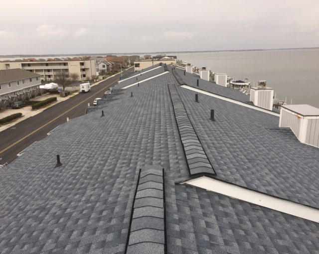 asphalt shingles on roof with view of body of water and road