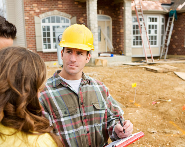 Roofer with homeowner reviewing checklist