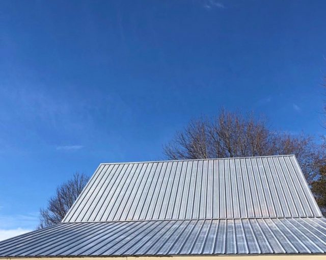 A silver colored metal roof installed on a commercial building