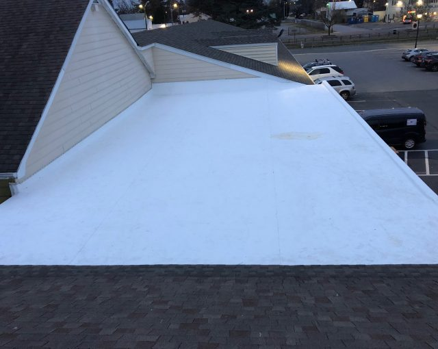 A flat roof with a white finish coating to control temperature