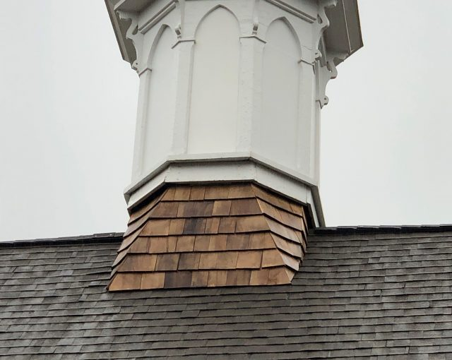 A white peak with a cedar shake and shingle roof
