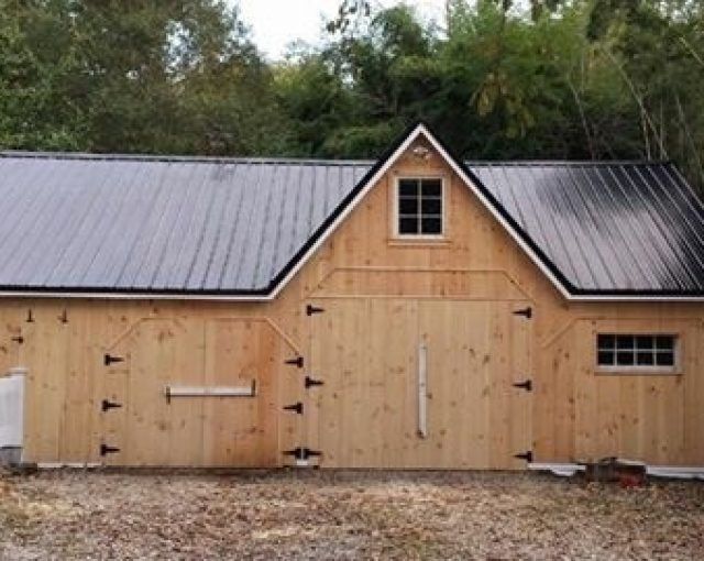 A black metal roof on a wooden barn